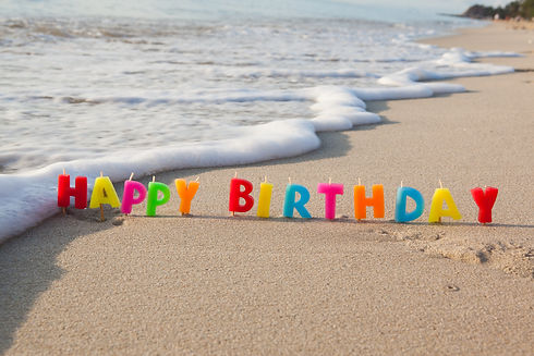Happy birthday candles on a beach..jpg