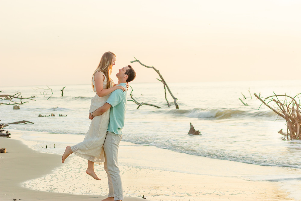 Sam and Jenna have romantic sunrise photoshoot on the beach. Husband lifts wife while waves crash in the background