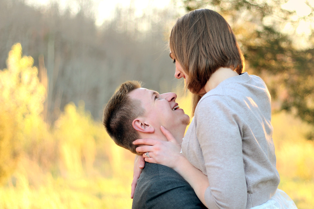 A couple are glowing with love for each other after kissing at sunset