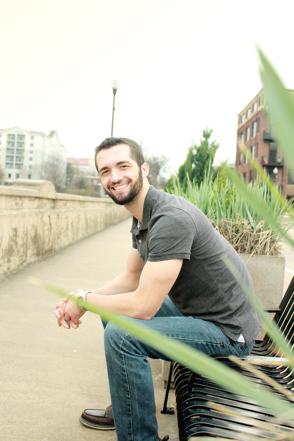 Exeter photographer sitting on a park bench and smiling for the camera