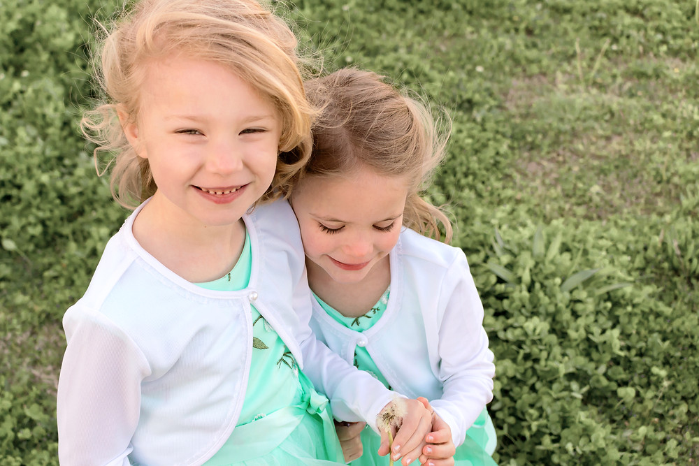 Two little girls wear matching outfits during a photo session with Sam and Jenna Photography