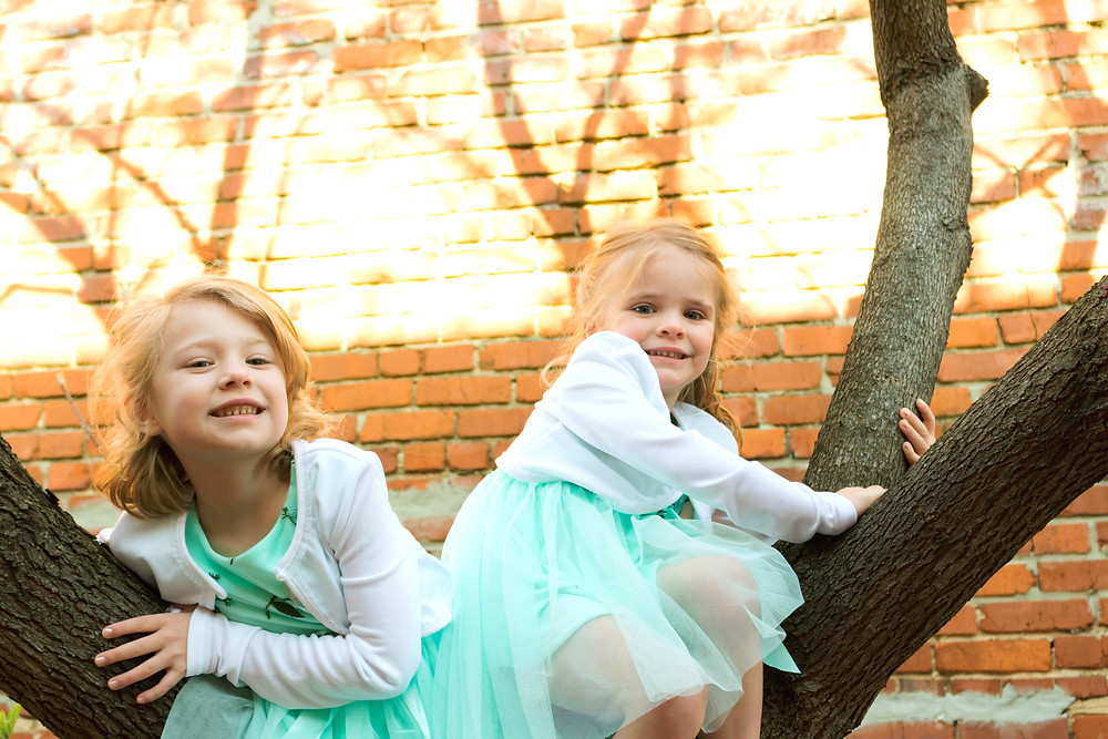 Two sisters climb a tree while wearing matching turquoise dresses
