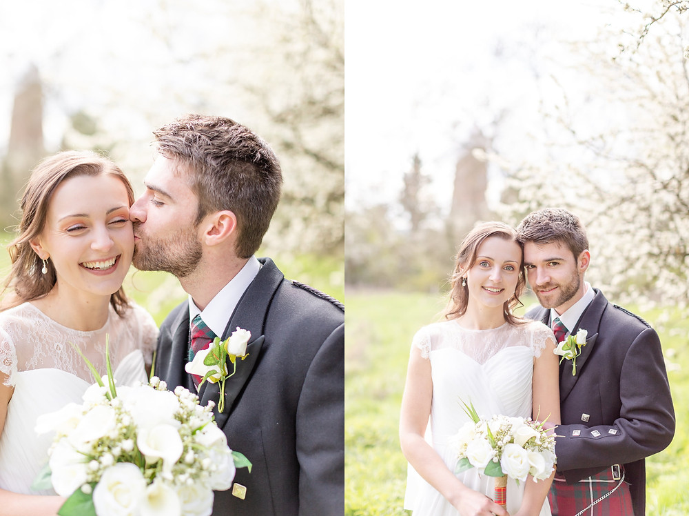 bride and groom smile at the camera, groom kisses bride on the cheek during portraits with Sam and Jenna Photography, Devon wedding photographer