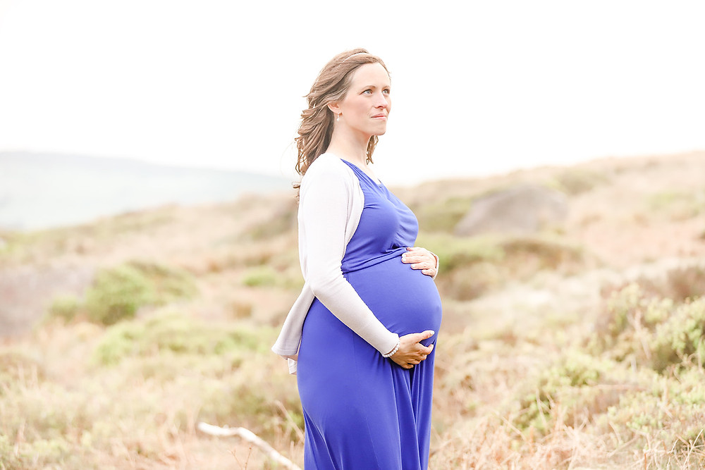 Gorgeous expectant Mother holds her tummy while looking out over the Peak District National Park