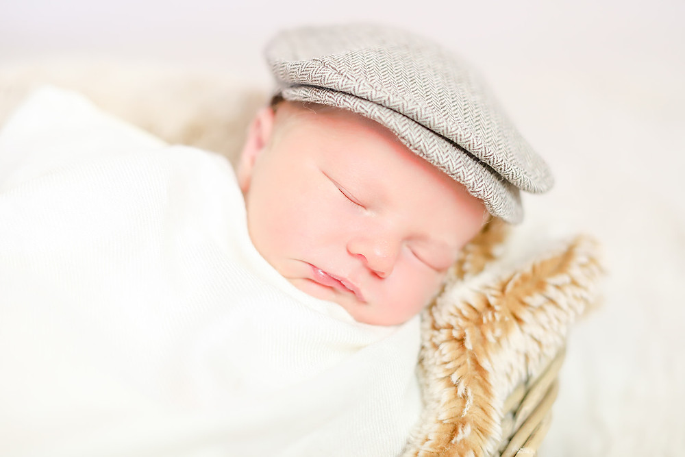 Close up photo of a newborn baby boy's face as he sleeps wearing a flat cap