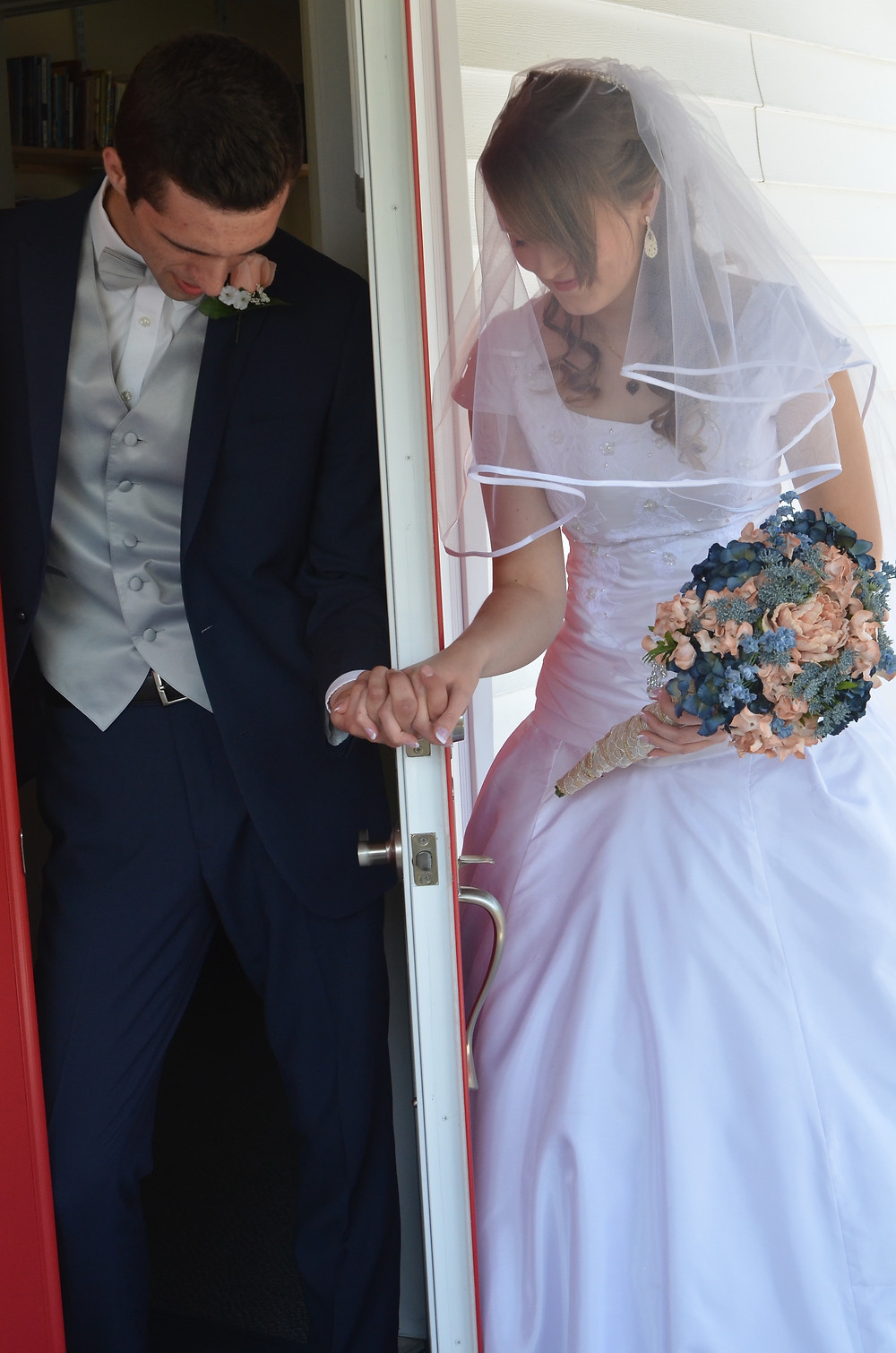 A bride and groom hold hands with a door separating them and pray together before the wedding ceremony