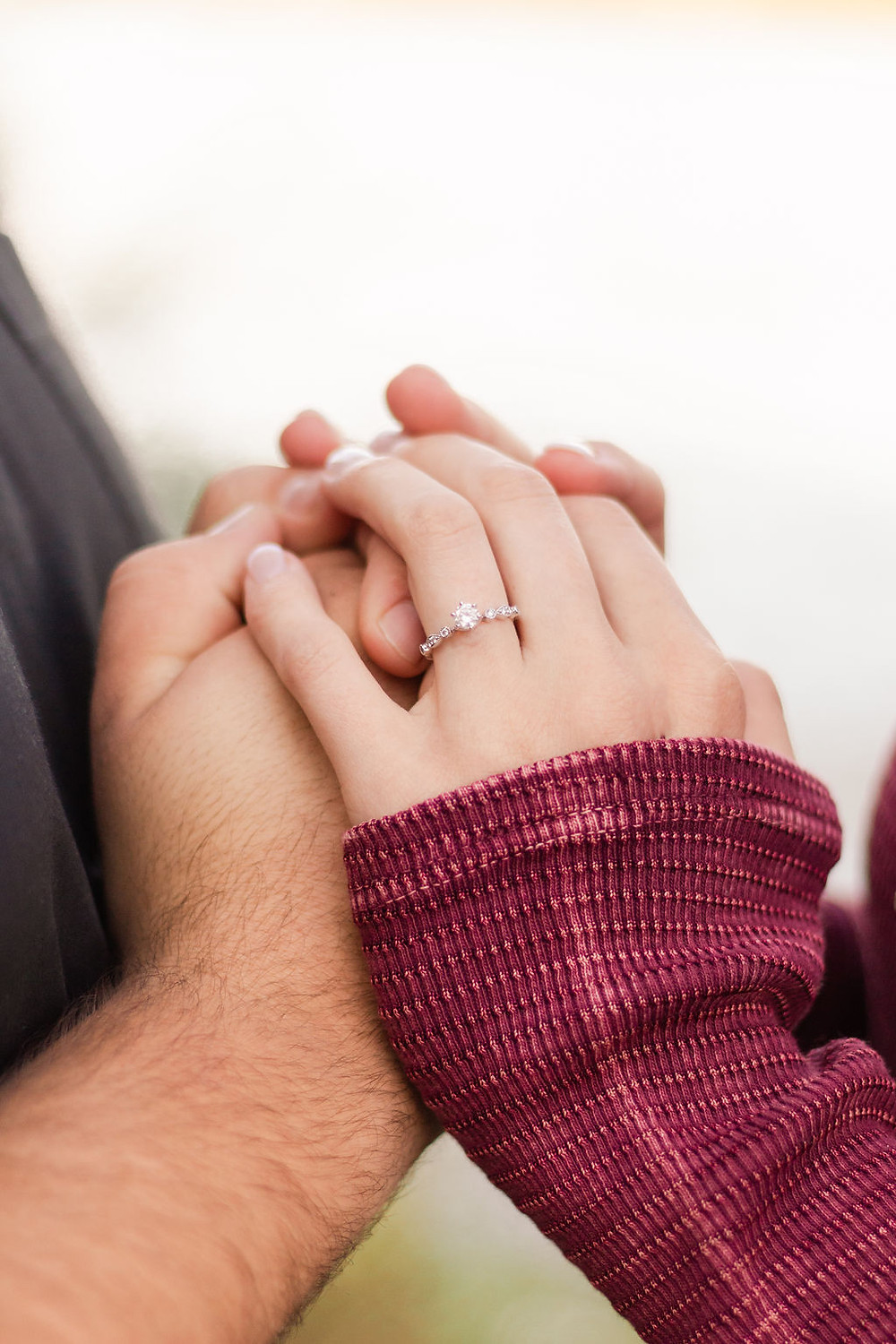 close up of an engagement ring, woman puts her hands on her fiancé's hands
