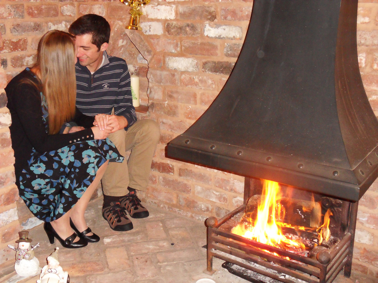 A couple are newly engaged and snuggle near a romantic fireplace