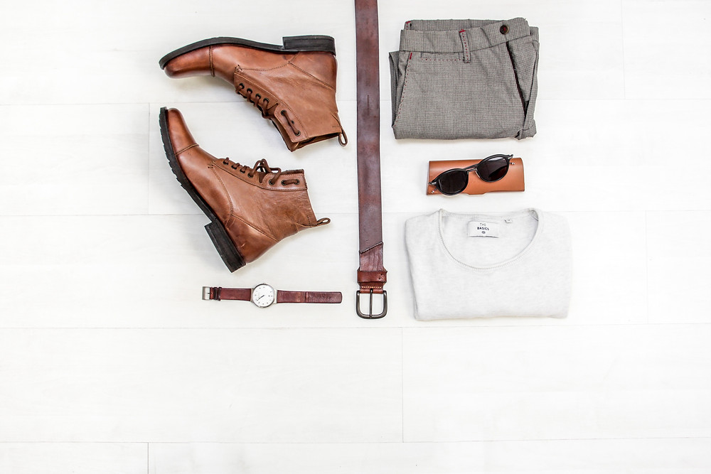 mens brown leather shoes, brown leather belt, wristwatch, taupe patterned trousers, cream coloured shirt, sunglasses on tip of a brown leather sunglass case