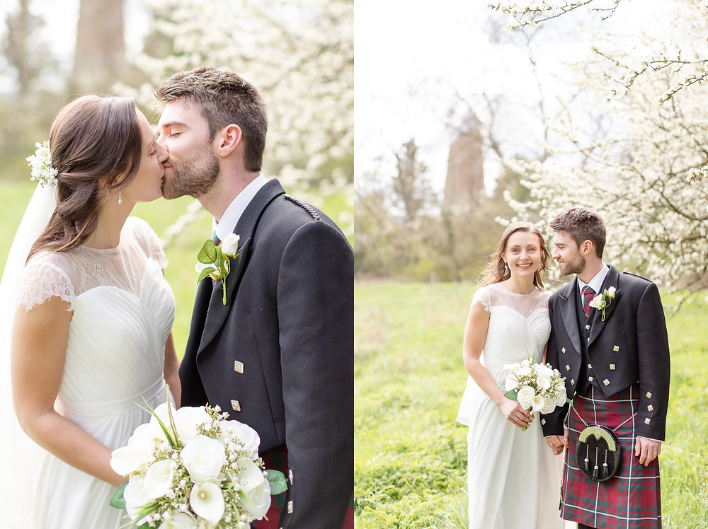 bride and groom kiss under white blossom trees. bride smiles and groom looks at bride, a windmill in Quainton is visible in the background