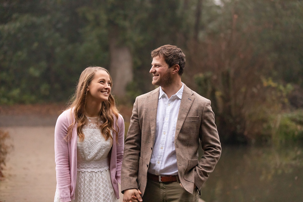 a young couple hold hands and laugh