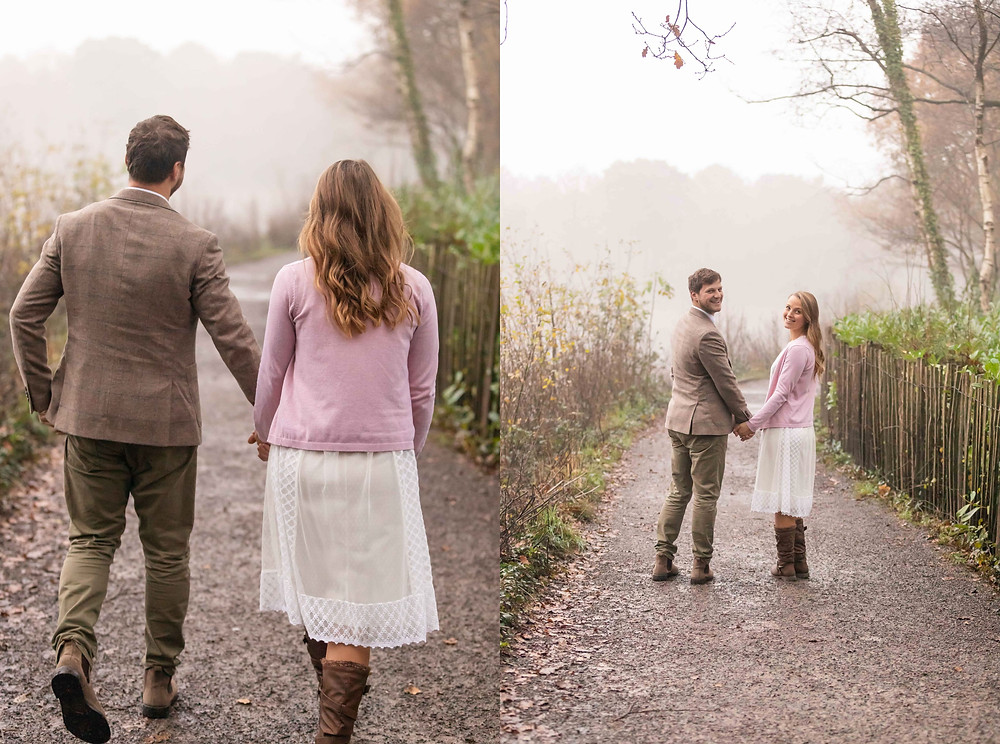 a happy couple holds hands and walks down a dreamy path and look back over their shoulders at Exeter portrait photographers, Sam and Jenna Photography