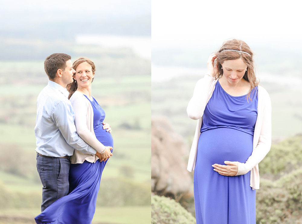 Pregnant couple stand together smiling in front of green fields and a lake in the Peak District National Park