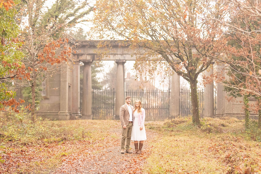 Beautiful Fall Scence with a couple stood in front of a park gatehouse