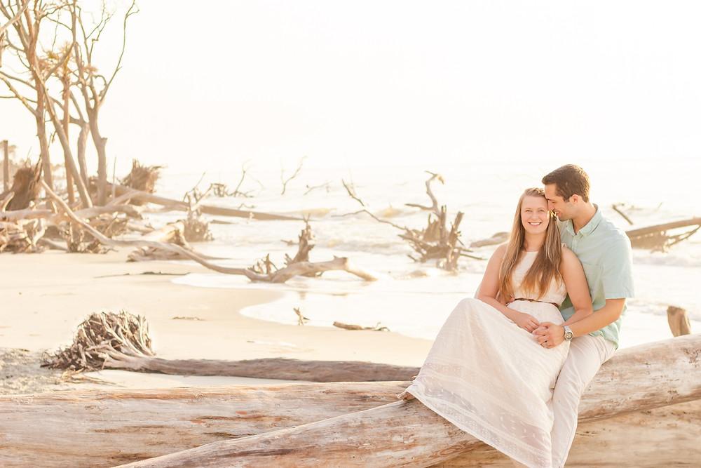 Devon wedding photographers Sam and Jenna sit on a fallen tree during their beach sunrise photoshoot for their anniversary