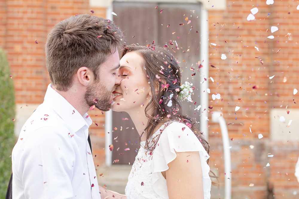 close up photo of a gorgeous bride and groom kissing as they are showered with pink petals and biodegradable confetti