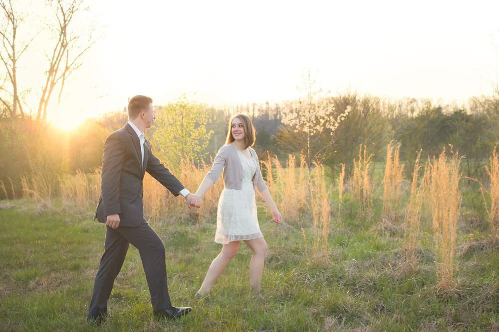 A well dressed couple stroll through a gorgeous meadow at sunset