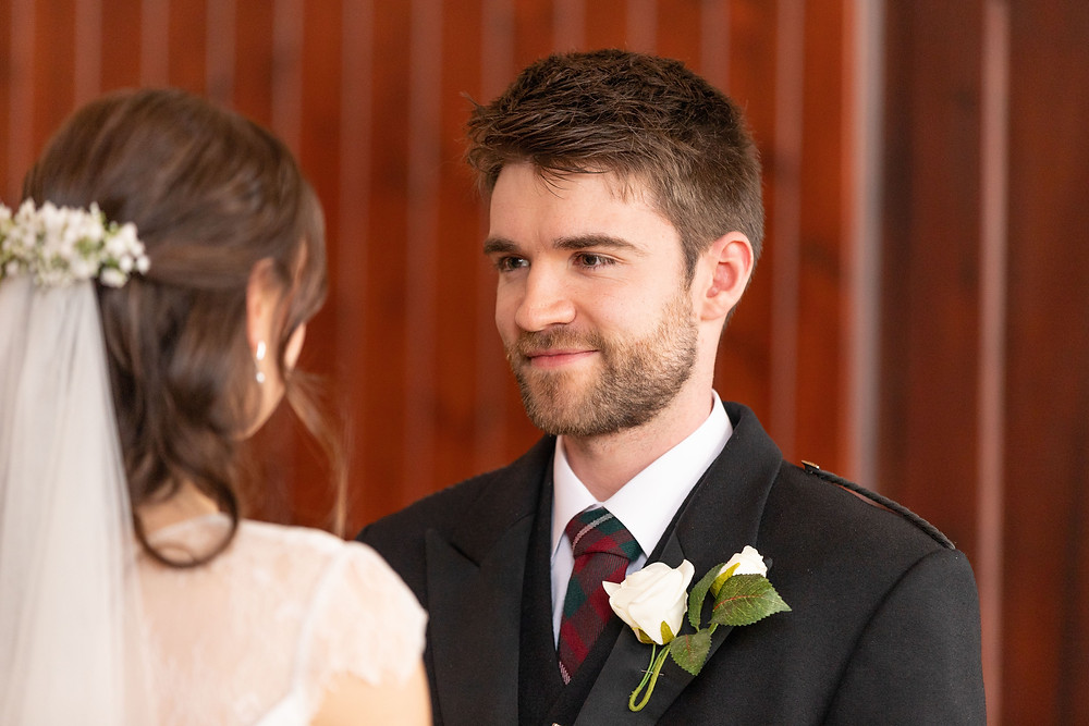 groom smiles at bride while she recites her wedding vows