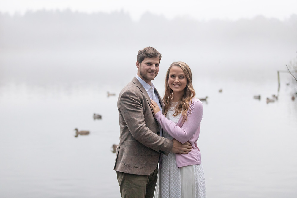 A newly engaged couple stand in front of a misty lake while ducks swim behind them
