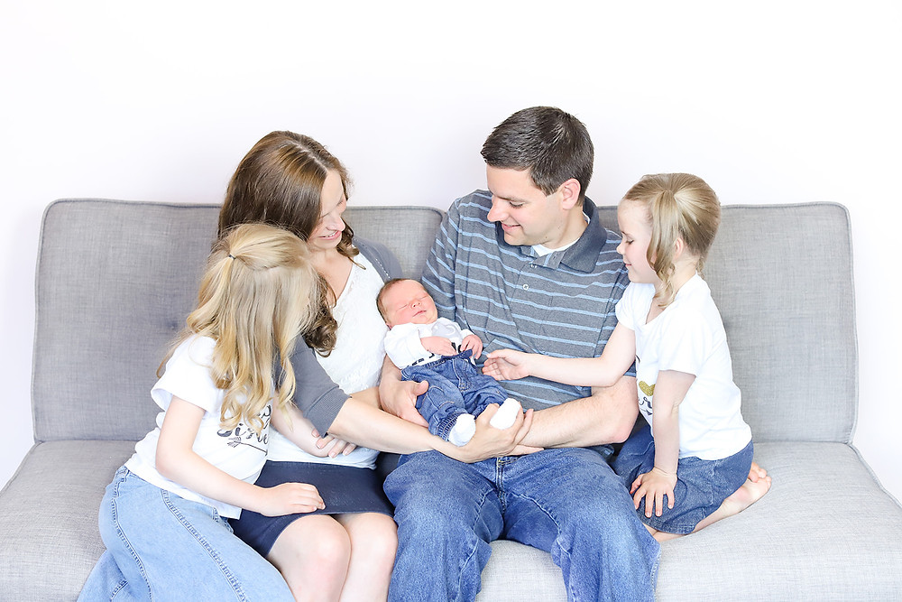 Photo of young family sitting on the sofa looking over their newborn baby, taken by exeter photographers