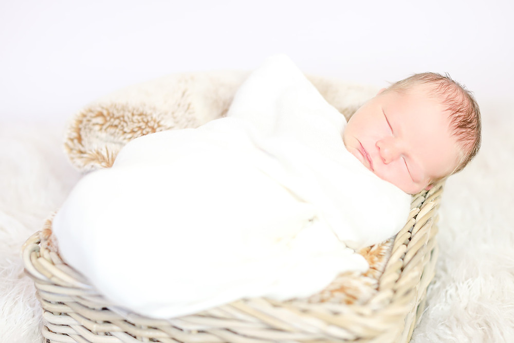 Newborn baby is swaddled in a cream wrap and sleeping peacefully in a basket