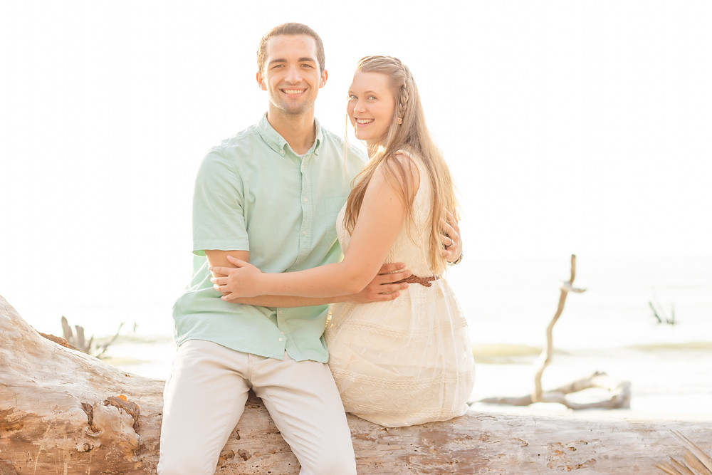 Couple smile at the camera during romantic beach photoshoot