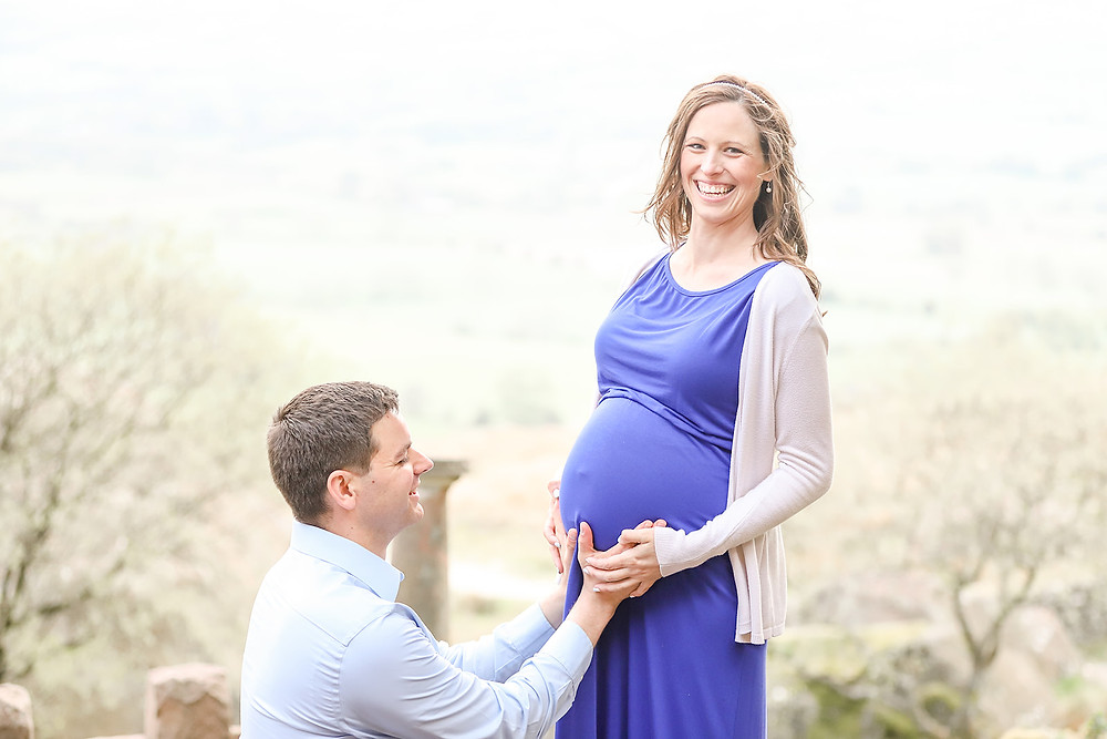 Beautiful couple pose for maternity photoshoot, they both laugh as Dad touches Mum's tummy