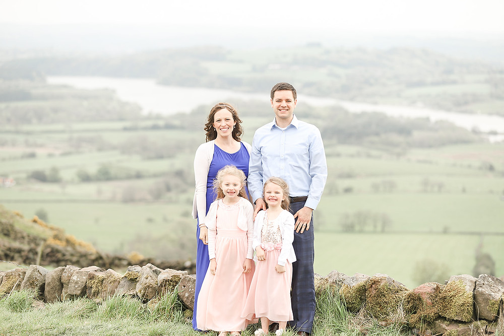 A family of four smile at the camera with a gorgeous background of hills, forests, and a river in the Peak District