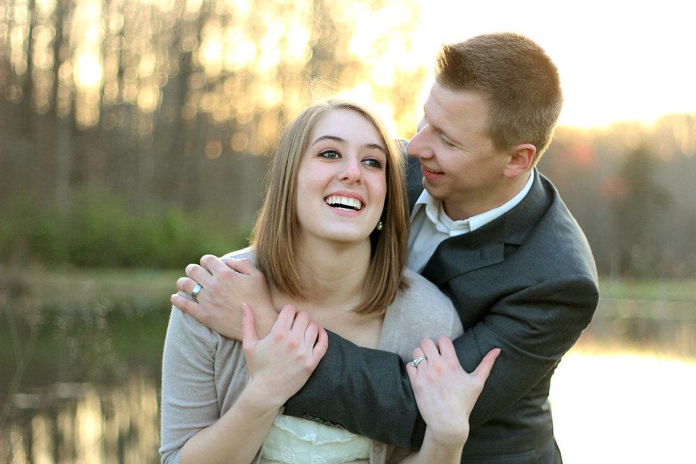 A man in a suit hugs his wife and they both are smiling during their golden light photoshoot near a lake with Devon wedding photographers