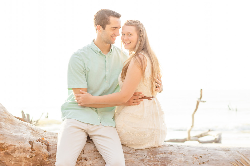 Man and wife sit on a log at the beach and hug each other