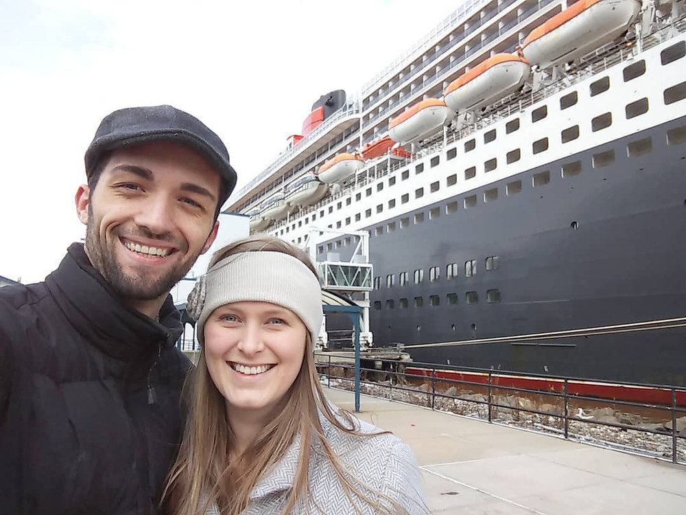 Couple take photo in front of the Queen Mary 2