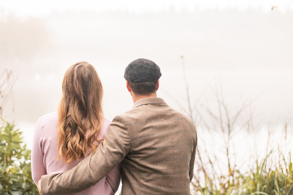 A dapper looking couple gaze over a misty lake at Stover Country Park