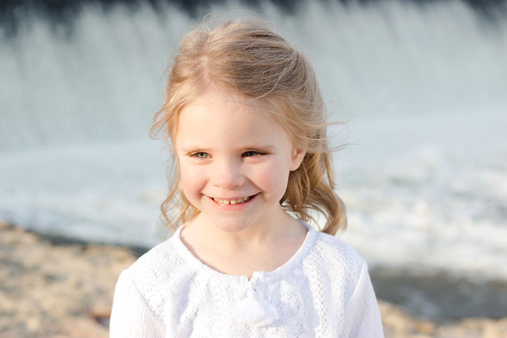 pretty little girl smiles in front of a waterfall