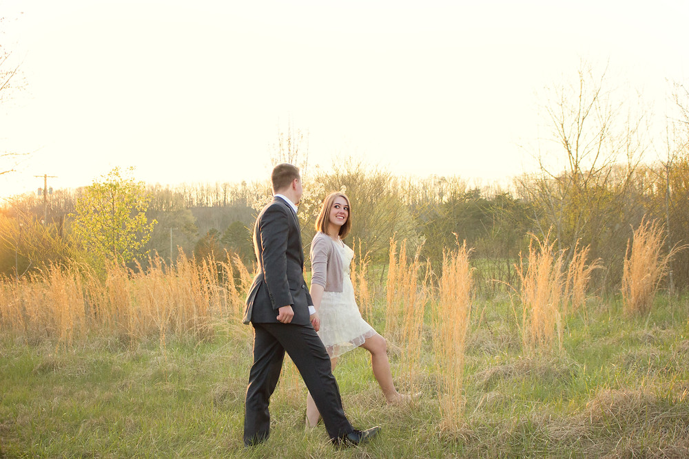 A man and woman stroll through a beautiful grassy field and look into each other's eyes during a sunset photo shoot with Devon wedding photographers, Sam and Jenna