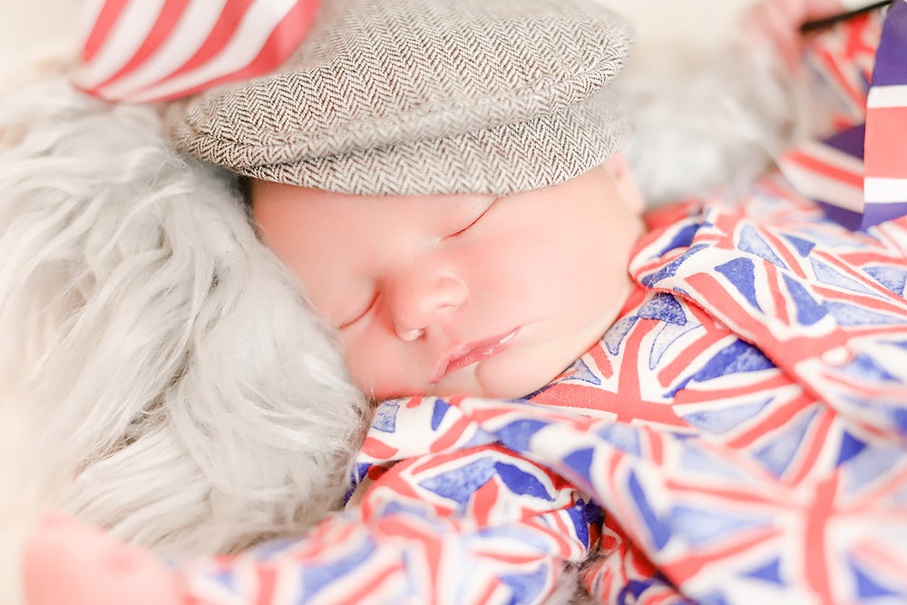 Close up photo of a newborn baby boy wearing a flat cap and a Union Jack onesie