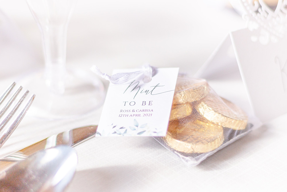 """Detail photo of a wedding favour bag filled with chocolate mints and a tag that says """"Mint to be"""""""