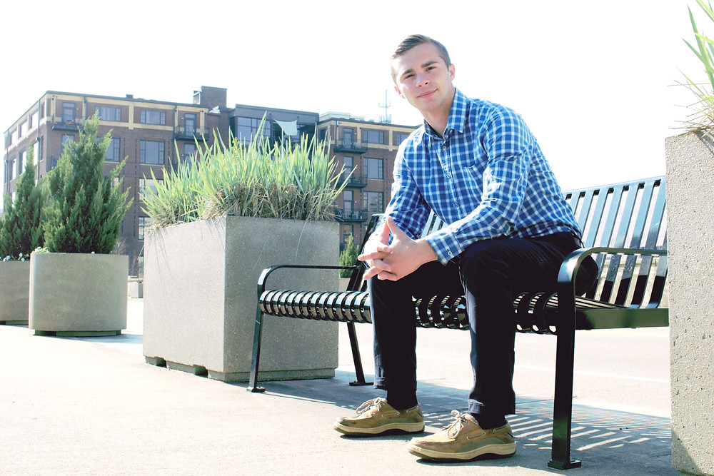 Epic photo of a man in his twenties sitting on a bench during his photoshoot