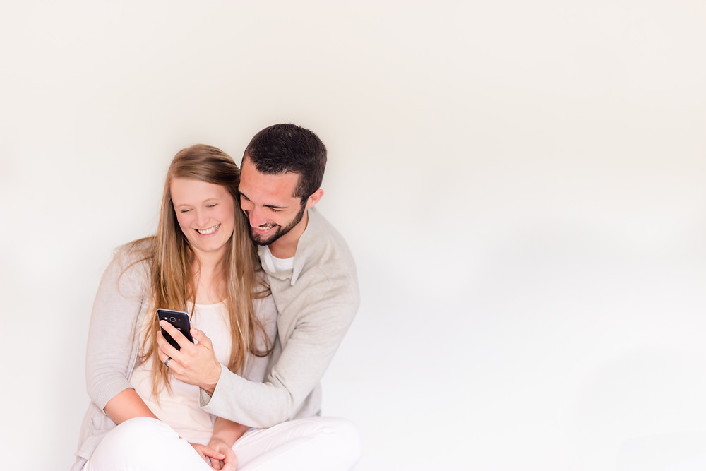 A happy couple looking at photos and laughing