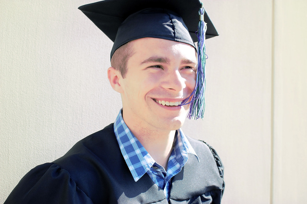 Graduate smiles while wearing cap and gown