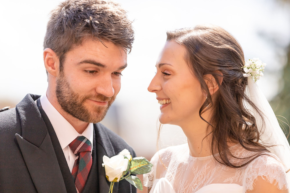bride and groom share a laugh after coming out of the wedding ceremony
