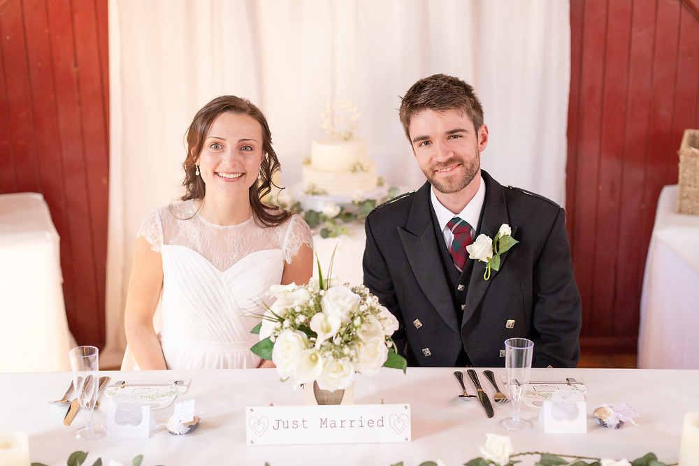 Bride and groom smile as they sit at their reception table with their wedding cake in the background