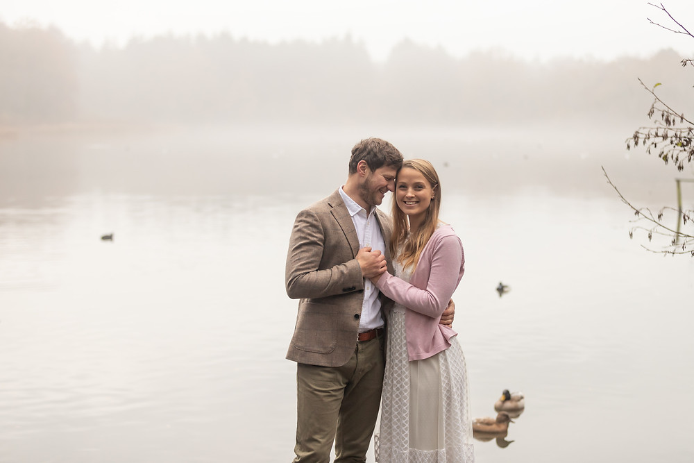 A future bride and groom hold hands in front of a mistry duck pond during a dreamy sunrise engagement shoot with Devon wedding photographers, Sam and Jenna Photography