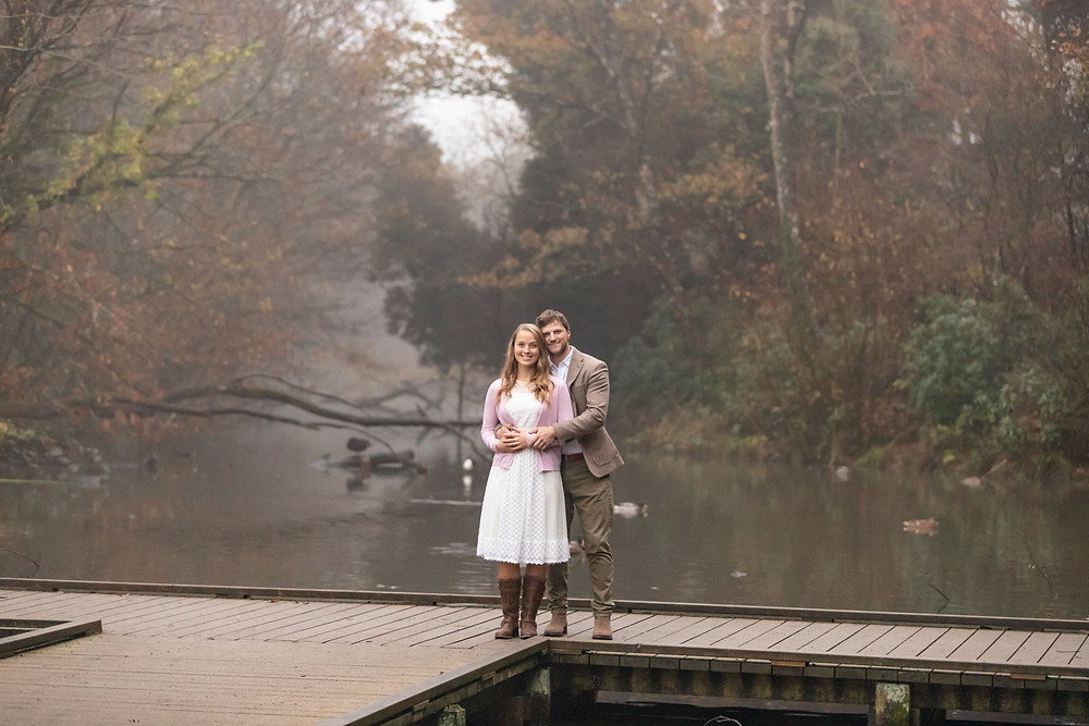 an adorable couple embrace while standing on a footbridge with water underneath and behind them