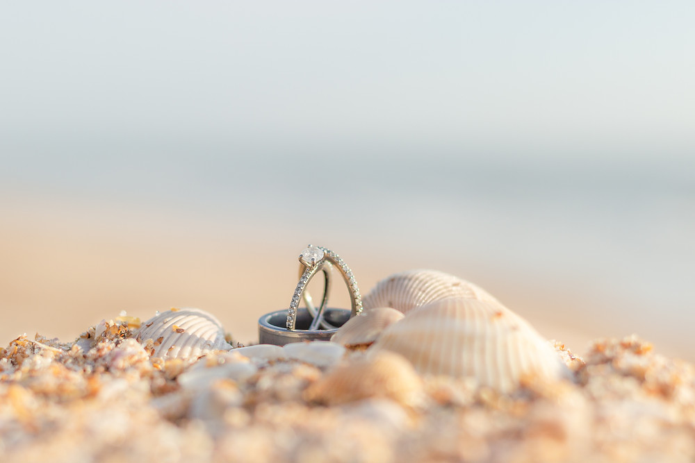 Beach detail photo of wedding and engagement rings surrounded by sand and seashellls