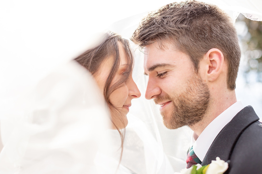 bride and groom enjoy a tender moment under the wedding veil and smile at eachother