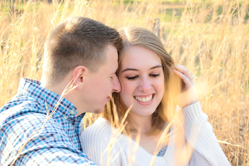 Light and airy photo of a happy couple sitting in a gorgeous, grassy field during a gorgeous sunset