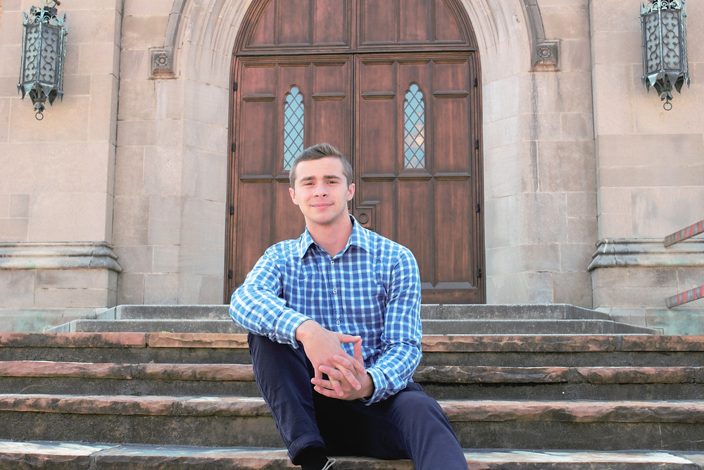 Young man sits in front old church doors during a session with Devon photographers