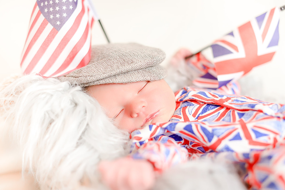 Newborn baby sleeps on a furry blanket while wearing a Union Jack onesie and waving a British and American flag