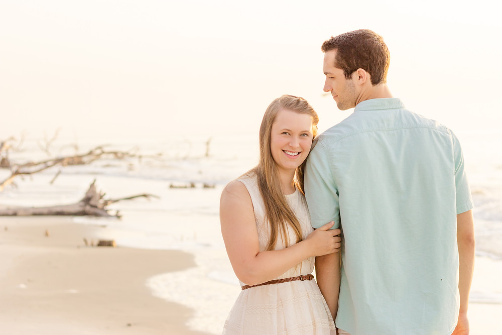 Woman wearing beautiful dress holds man's arm and smiles at the camera with sandy beach coastline in the background