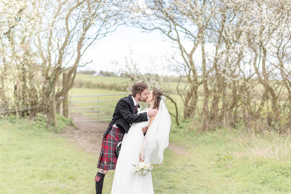 bride and groom share a tender kiss underneath blossom trees